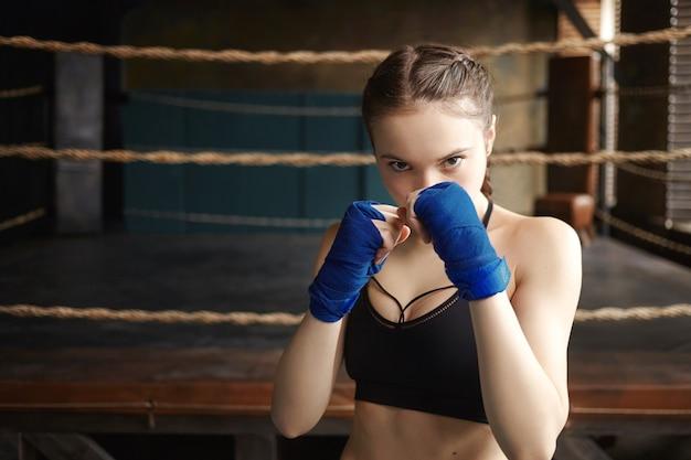 Sport, vastberadenheid, fitness en vechtsporten. sportief meisje dragen zwarte droge fit top en boksbandages permanent in defensieve houding, Gratis Foto