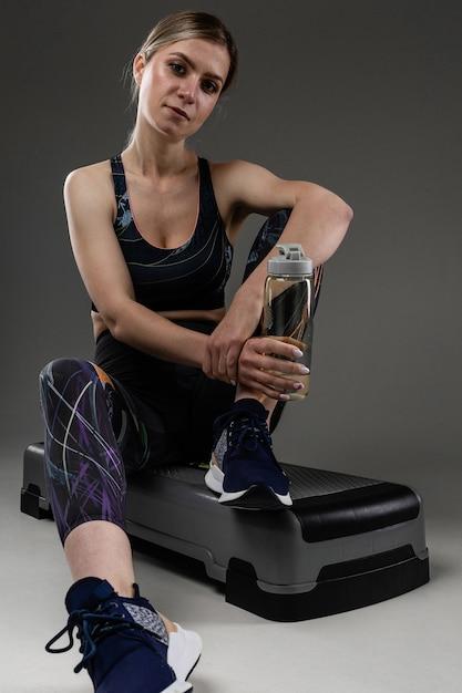 Sport vrouw zit met fles water na de training en ontspannen Premium Foto