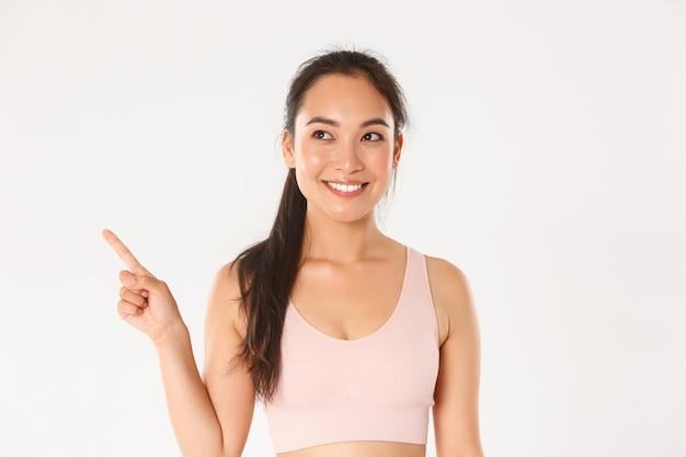 Sport, welzijn en actief levensstijlconcept. close-up van glimlachend aantrekkelijk aziatisch geschiktheidsmeisje, vrouwelijke atleet die nieuwe spullen in opslag plukken, en linkerbovenhoek tevreden kijkt. Gratis Foto