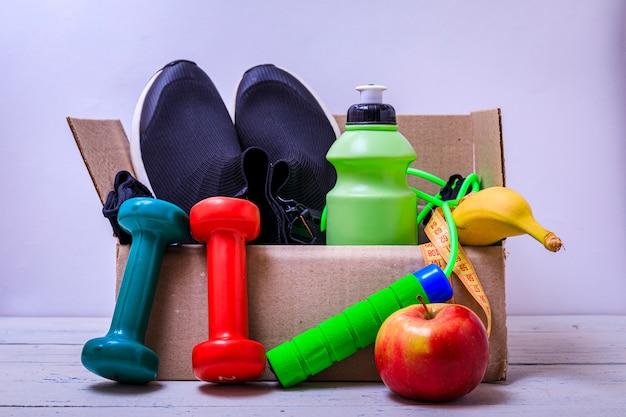 Sportartikelen voor donaties in de doos. sportschoenen, appel, flessen water. liefdadigheidsactiviteit. Premium Foto