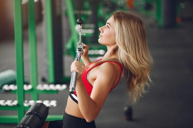 Sportblonde in sportkleding opleiding in een gymnastiek Gratis Foto