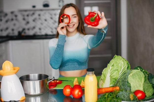 Sportenmeisje in een keuken met groenten Gratis Foto