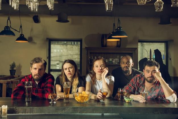 Sportfans juichen in bar, pub en drinken bier terwijl kampioenschap, competitie gaat Gratis Foto