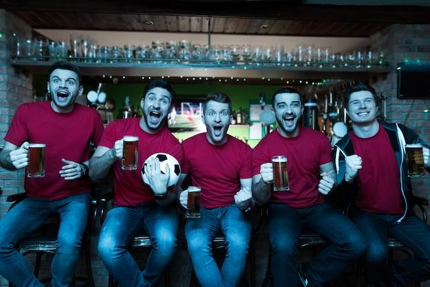 Sportfans vieren en bier drinken in de bar. Premium Foto