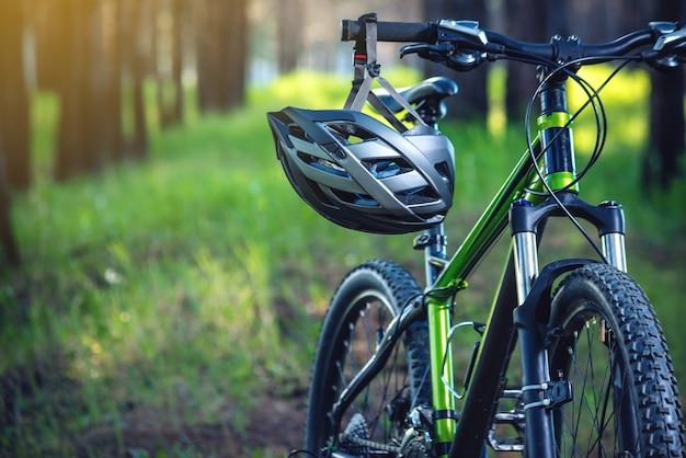 Sporthelm op een groene mountainbike in het park. conceptbescherming tijdens actieve en gezonde levensstijl Premium Foto