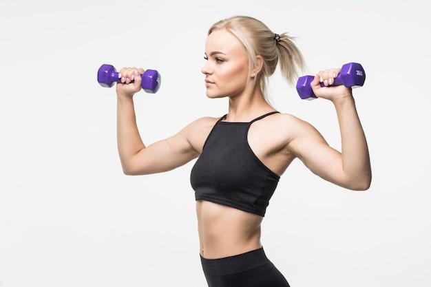 Sportief blond jong meisje met fit gespierd lichaam werkt met halters in studio op wit Gratis Foto