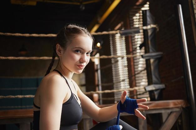 Sportief meisje met vlechten binnenshuis zitten, pleisters inwikkeling op haar handen, strijd voorbereiden. mooie jonge sportvrouw in zwarte bovenkant Gratis Foto