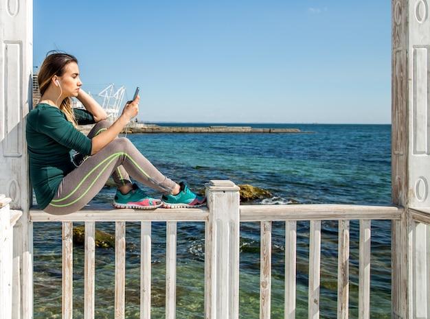 Sportief meisje op de pier met de telefoon Gratis Foto