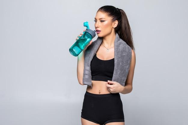 Sportief spiervrouwen drinkwater, dat tegen witte muur wordt geïsoleerd Gratis Foto