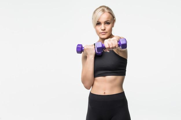 Sportief vrij blond jong meisje met fit gespierd lichaam werkt met halters in studio op wit Gratis Foto