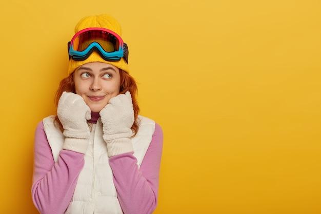 Sportieve atletische meisjesskiër kijkt peinzend opzij, draagt witte winterhandschoenen en vest, snowboardbril, kijkt opzij, poseert tegen gele studiomuur, lege ruimte Gratis Foto