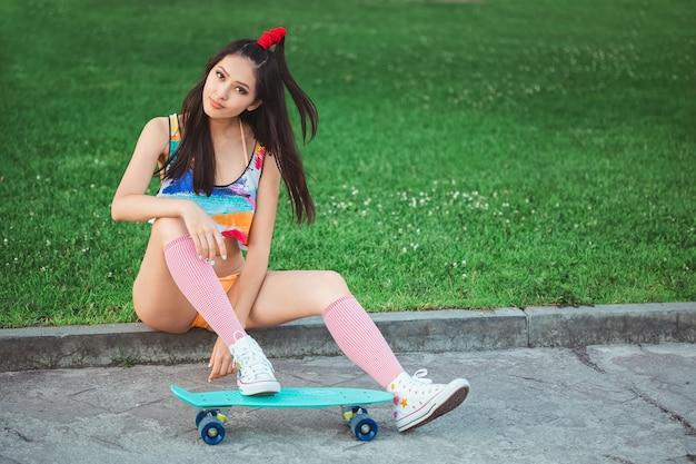 Sportieve aziatische vrouw met skateboard Premium Foto