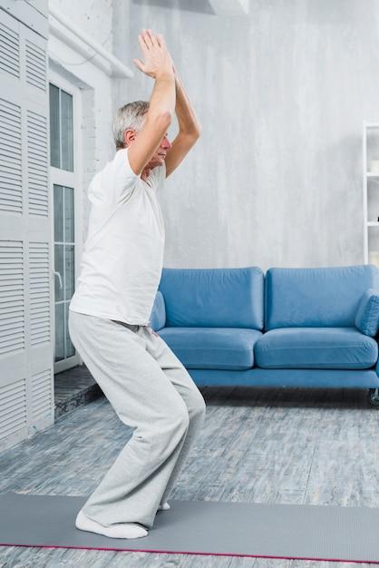 Sportieve bejaarde beoefenen van yoga binnenshuis Gratis Foto