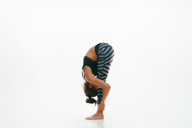 Sportieve jonge vrouw die yogapraktijk doet die op witte muur wordt geïsoleerd. fit flexibel vrouwelijk model oefenen. concept van een gezonde levensstijl en natuurlijk evenwicht tussen lichaams- en mentale ontwikkeling. Gratis Foto