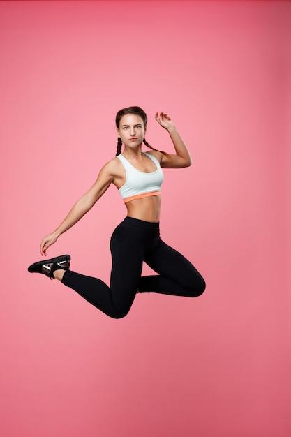 Sportieve jonge vrouw in blauwe top springen op zoek recht Gratis Foto
