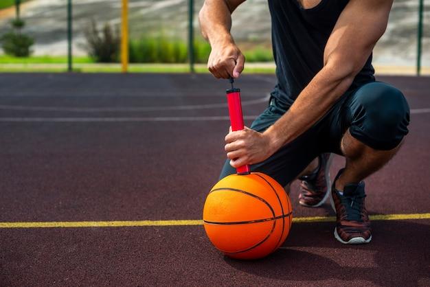 Sportieve man die een bal opblaast Gratis Foto