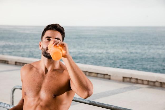 Sportieve man hydratatieproces na het sporten Gratis Foto