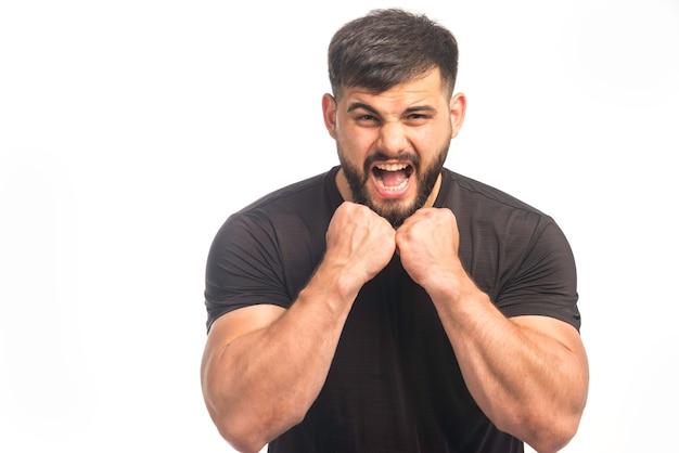 Sportieve man in zwart shirt met zijn vuisten Gratis Foto
