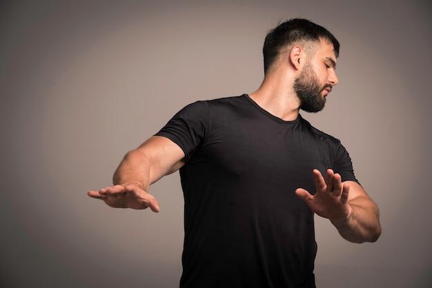 Sportieve man in zwart shirt verdedigt zichzelf en vermijdt vechten. Gratis Foto