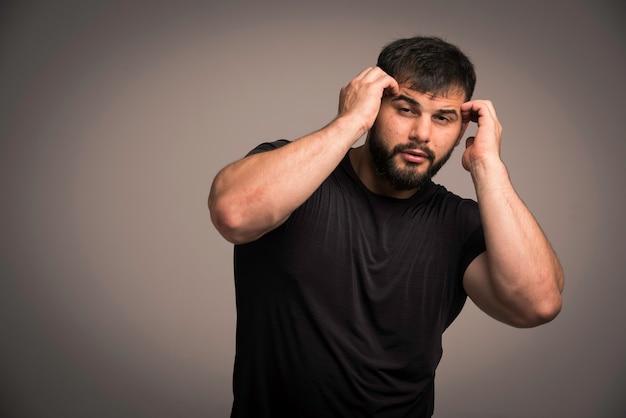 Sportieve man in zwart shirt verdedigt zichzelf. Gratis Foto