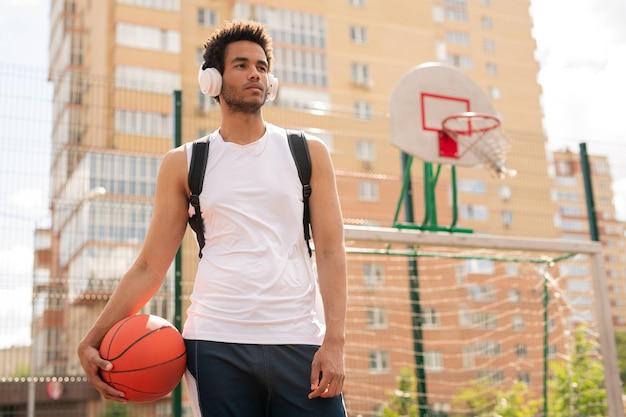 Sportieve man met bal voor het spelen van basketbal, luisteren naar muziek in koptelefoon op speelplaats van veld Premium Foto
