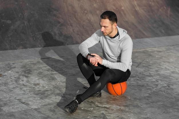 Sportieve man rust op een basketbal Gratis Foto
