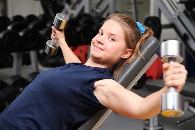 Sportieve meisje in sportkleding liggend op fitnessapparatuur training met halters op sportschool Premium Foto