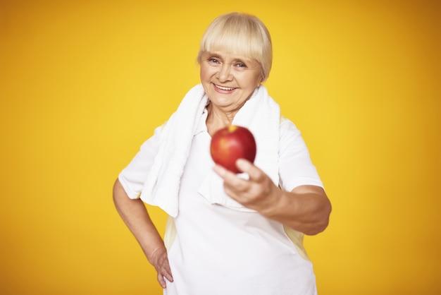 Sportieve oma biedt apple oefeningen voeding. Premium Foto