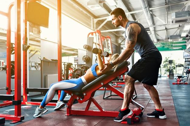 Sportieve vrouw die gewichtsoefeningen met hulp van haar persoonlijke trainer doet bij gymnastiek Premium Foto