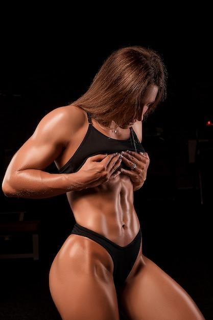 Sportieve vrouw die haar afgezwakte buikspieren bekijkt Premium Foto