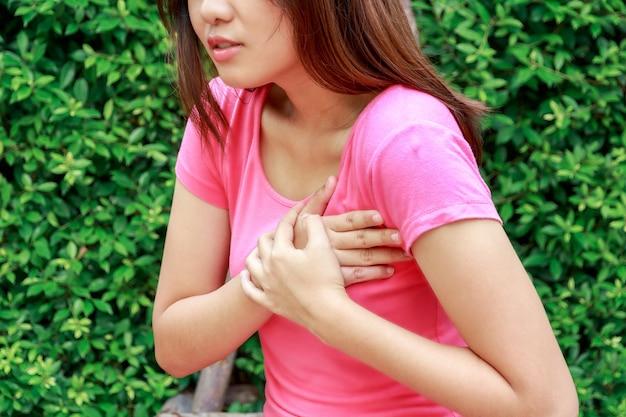 Sportieve vrouw die hartaanval bij openlucht heeft - angina pectoris, myocardiaal infarct. Premium Foto