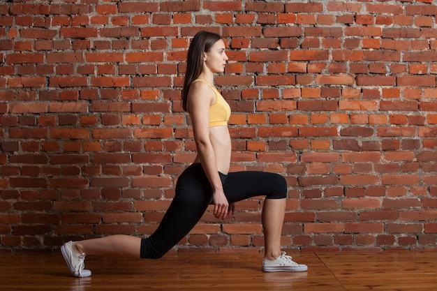 Sportieve vrouw doet longe squat Premium Foto
