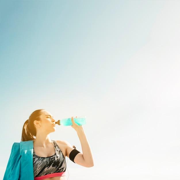 Sportieve vrouw drinken uit de fles op hemelachtergrond Gratis Foto