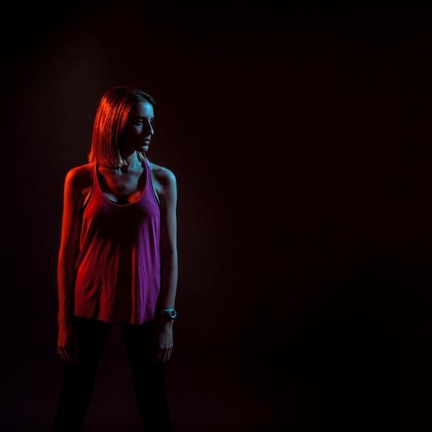 Sportieve vrouw in donkere neonlichten Gratis Foto