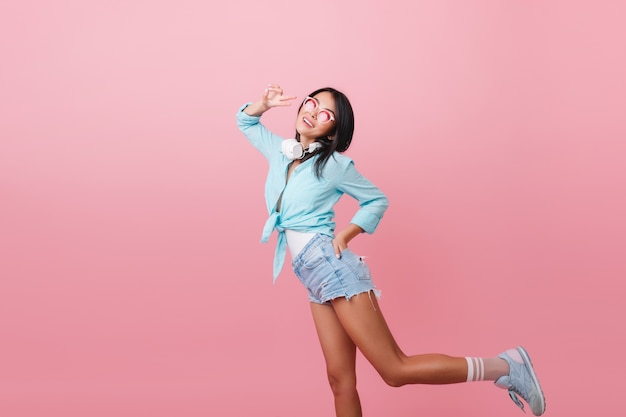 Sportieve vrouw met bronzen huid grappig dansen met positieve gezichtsuitdrukking. bevallig latijns-meisje in blauwe kleding die zich voordeed op één been. Gratis Foto