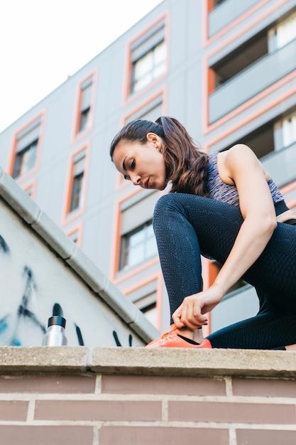 Sportieve vrouwen bindende schoenen op bakstenen muur Gratis Foto