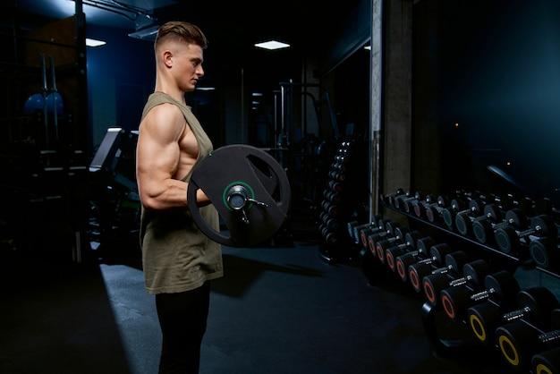 Sportman bouwen biceps met barbell. Gratis Foto