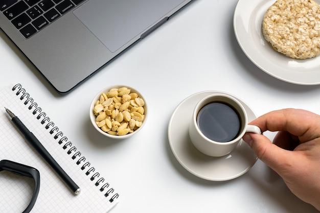 Sportman die knapperige rijstrondes met pinda's, kop van koffie eten dichtbij laptop Premium Foto