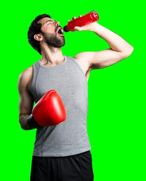 Sportman met bokshandschoenen drinkwater frisdrank Gratis Foto