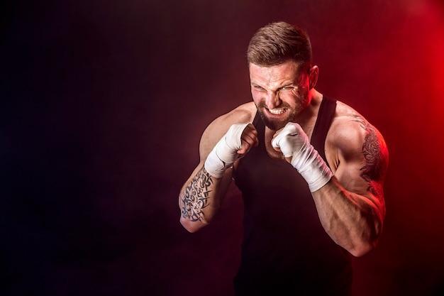 Sportman muay thai bokser vechten op zwarte achtergrond met rook. Premium Foto