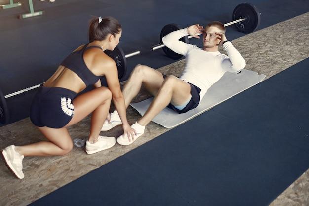 Sportpaar in sportkleding opleiding in een gymnastiek Gratis Foto