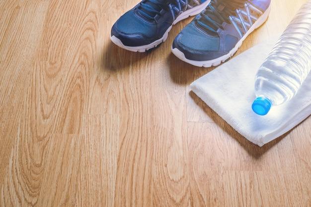 Sportschoenen, water, handdoek op hout Premium Foto