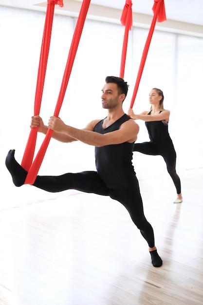Sporttrainers doen yoga-activiteiten met beddengoed Gratis Foto