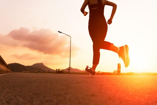 Sportvrouw die op een weg loopt. geschiktheidsvrouw opleiding bij zonsondergang Premium Foto