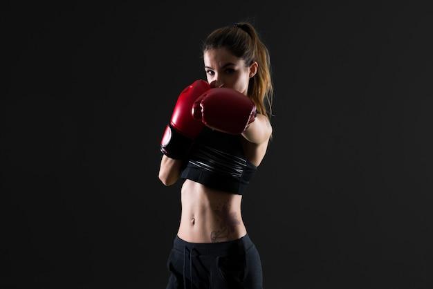Sportvrouw met bokshandschoenen op donkere achtergrond Premium Foto