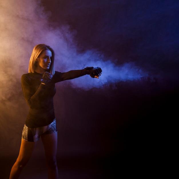 Sportvrouw opleidingsdoos in donkere studio Gratis Foto