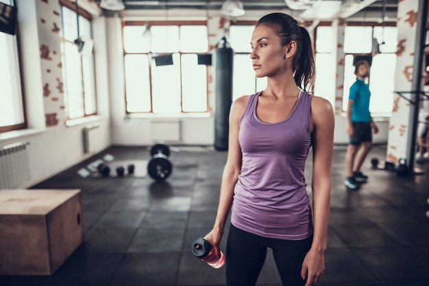 Sportvrouw staat in gymnastiek met fles water. Premium Foto