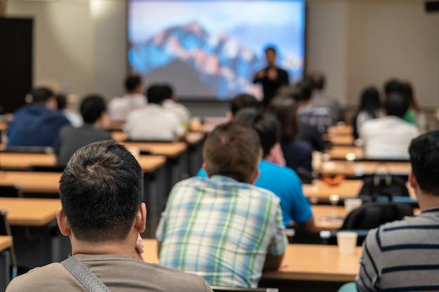 Spreker op het podium voor de kamer met achteraanzicht van publiek in handoplegging Premium Foto