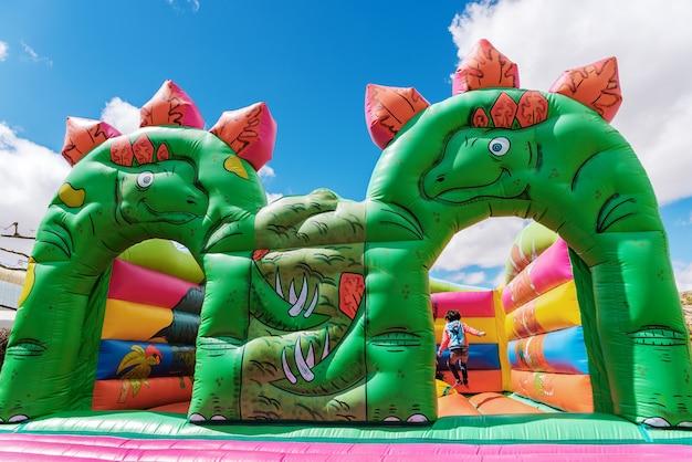 Springkasteel in de vorm van dinosaurussen in een speelplaats voor kinderen in openlucht. Premium Foto