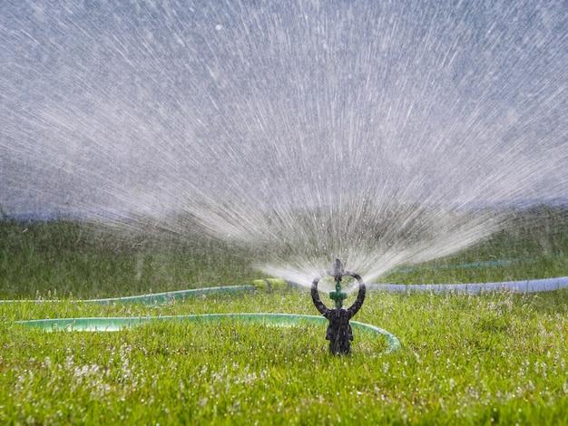 Sprinkler spatten het water naar groen grasveld, selecteer focus ondiepe scherptediepte Premium Foto